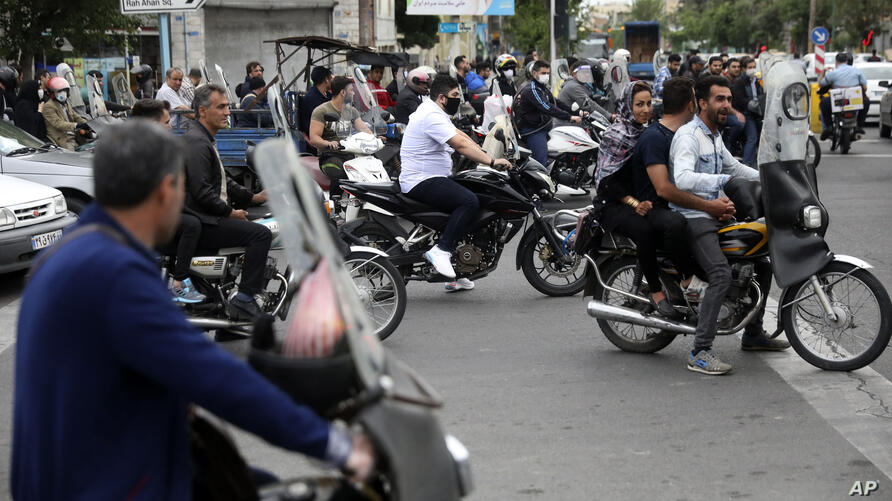 People on their motorcycles wait for a green light at an intersection in southern Tehran, Iran, Wednesday, April 29, 2020. Iran…