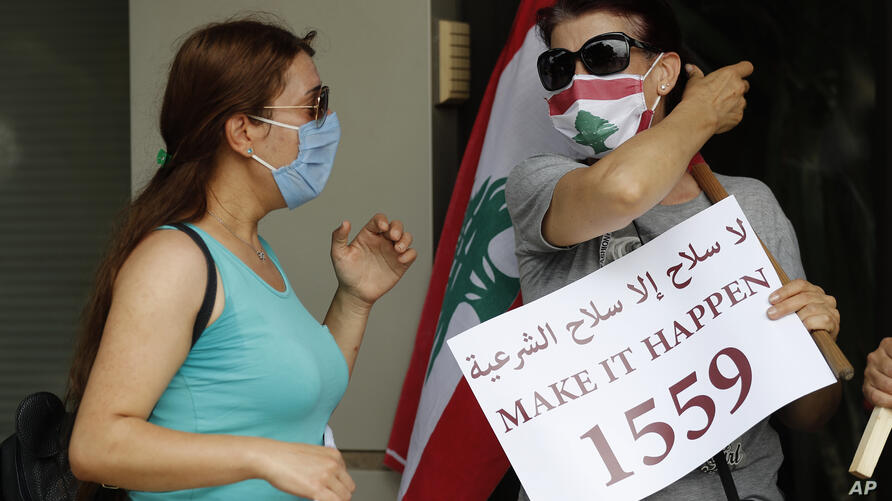 An anti-Hezbollah protester holds a placard with the U.N. Resolution 1559, which was adopted in Sept., 2004, that called for…