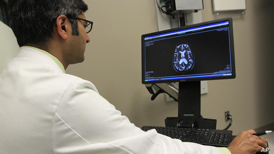 Dr. Punit Agrawal reviews Kathleen Sanford's MRI before her appointment Monday, Dec. 17, 2012, in Columbus, Ohio. Sanford is an…