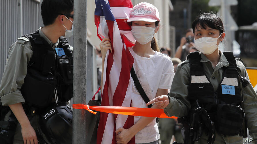 A protester carrying an American flag as she is stopped by riot police during a protest outside the U.S. Consulate in Hong Kong…