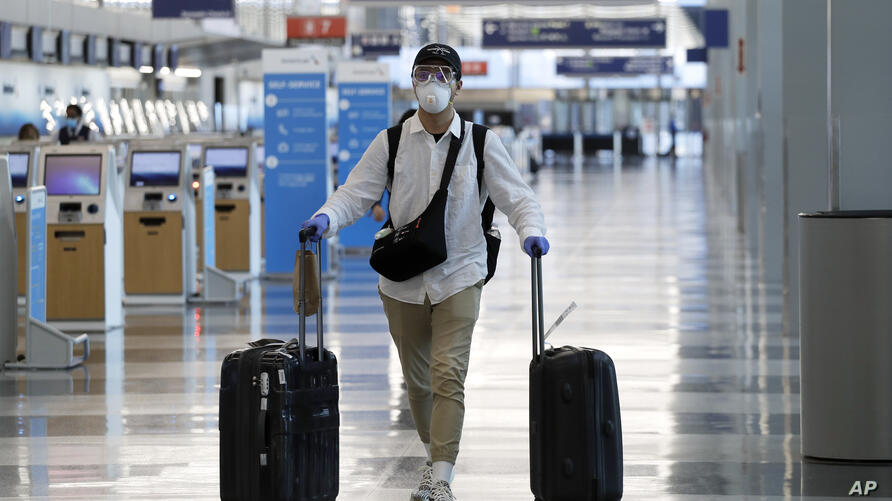 A traveler wears a mask and protective goggles as he walks through Terminal 3 at O'Hare International Airport Tuesday, June 16,…