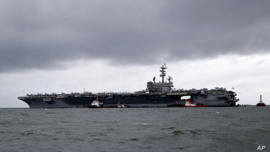 FILE - In this Aug. 7, 2019, file photo, rain clouds loom over the U.S. aircraft carrier USS Ronald Reagan as it is anchored…