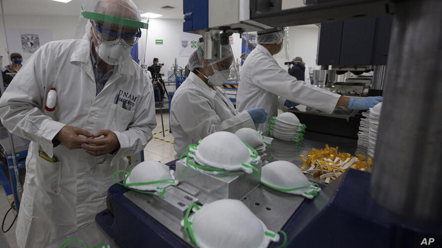 A supervisor inspects new face masks being made at a new factory in Mexico City, Thursday, May 21, 2020. An initiative by…