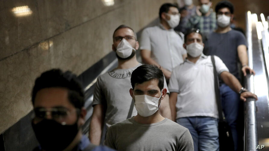People wear protective face masks to help prevent the spread of the coronavirus as they ride an escalator at a metro station,…