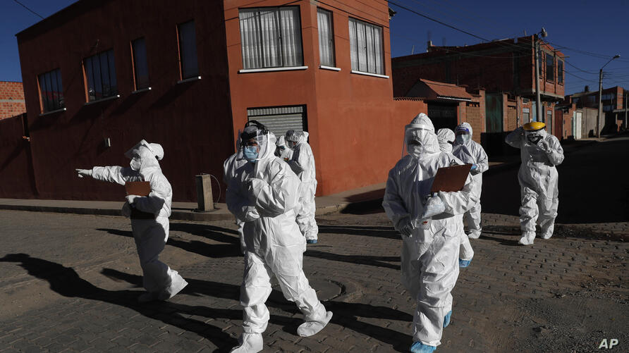 Dressed in full protective gear, doctors span out in a house-to-house new coronavirus testing campaign in the Villa Jaime Paz…