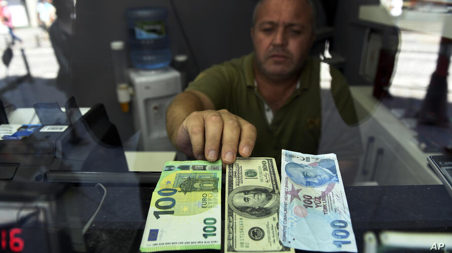 A currency exchange shop employee shows 100 Euros, 100 U.S. dollars and 100 Turkish Liras banknotes at his shop at a market…
