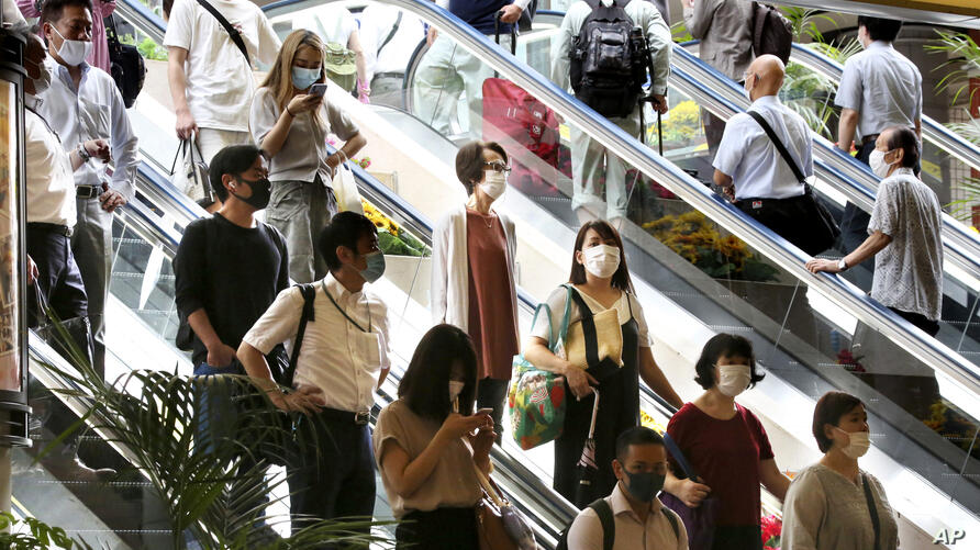 People wearing face masks to protect against the spread of the new coronavirus take an escalator at Yokohama station near Tokyo…