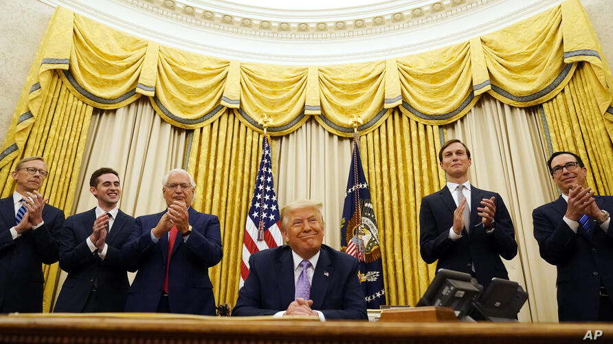 President Donald Trump is applauded after speaking in the Oval Office at the White House, Thursday, Aug. 13, 2020, in…