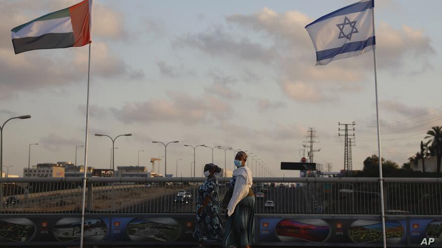 Women wearing face masks against the coronavirus walk past United Arab Emirates and Israeli flags at the Peace Bridge in…
