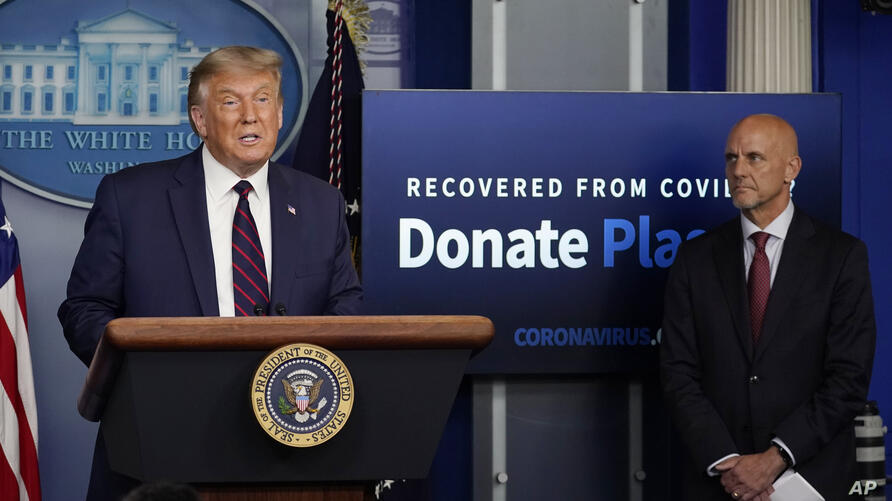 President Donald Trump speaks as Stephen Hahn, commissioner of the U.S. Food and Drug Administration, listens during a media…
