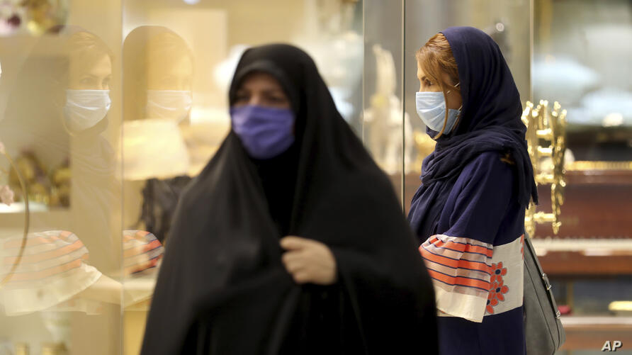 Women wearing protective face masks to help prevent spread of the coronavirus walk through a shopping center, in Tehran, Iran,…
