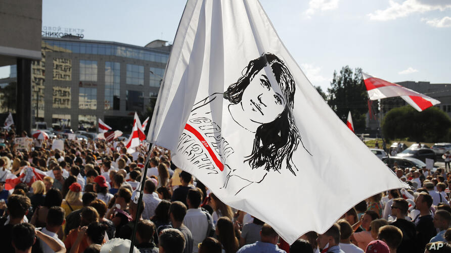People hold a flag with a portrait of Sviatlana Tsikhanouskaya, former candidate for the presidential elections, during a rally…