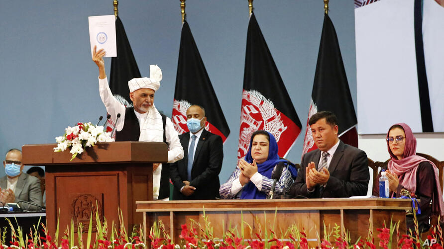 Afghan President Ashraf Ghani holds up the resolution on the last day of an Afghan Loya Jirga or traditional council, in Kabul,…