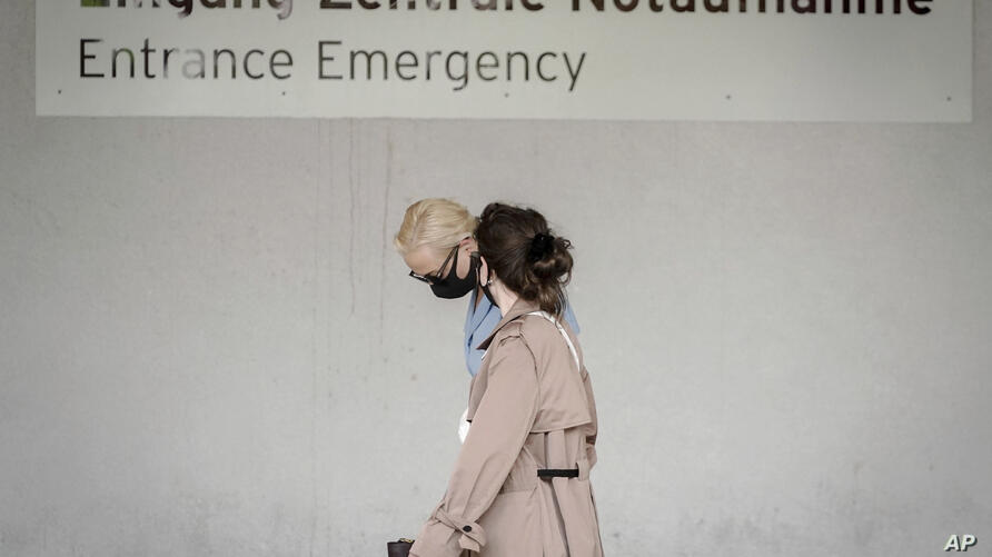 Alexei Navalny's wife Yulia, background, arrives at the Charite hospital in Berlin, Germany, Monday, Aug. 24, 2020. Russian…