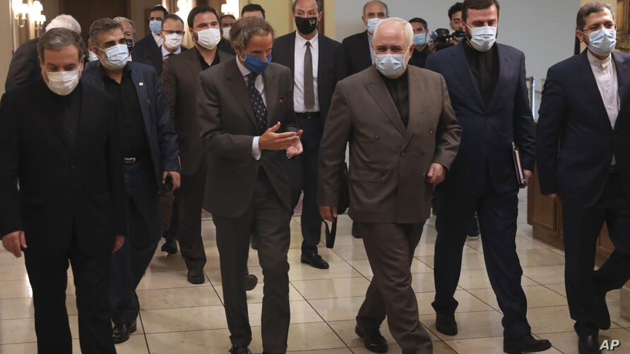Director General of International Atomic Energy Agency, IAEA, Rafael Mariano Grossi, center left, speaks with Iran's Foreign…