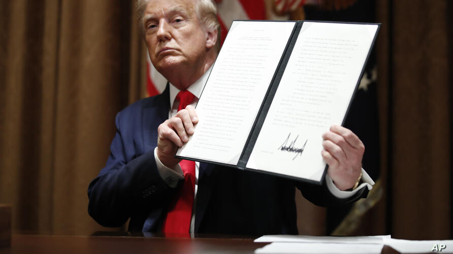 President Donald Trump holds up a signed Executive Order on hiring American workers, during a meeting with U.S. tech workers,…