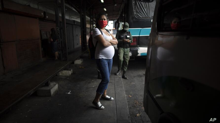 A pregnant woman wearing a protective face mask as a measure to curb the spread of the new coronavirus, waits for a bus in…