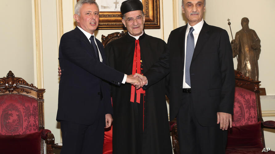In this photo released by Lebanese Forces group media office, Samir Geagea, leader of the Lebanese Forces group, right, shakes…