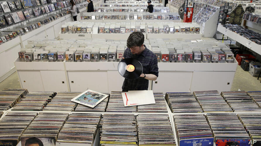 Record clerk Josh Kelly checks the condition of used LP records as he puts them in sales bins at Vintage Vinyl Records Tuesday,…