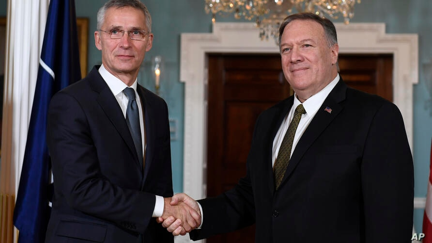 Secretary of State Mike Pompeo, right, shakes hands with NATO Secretary General Jens Stoltenberg, left, as they pose for a…