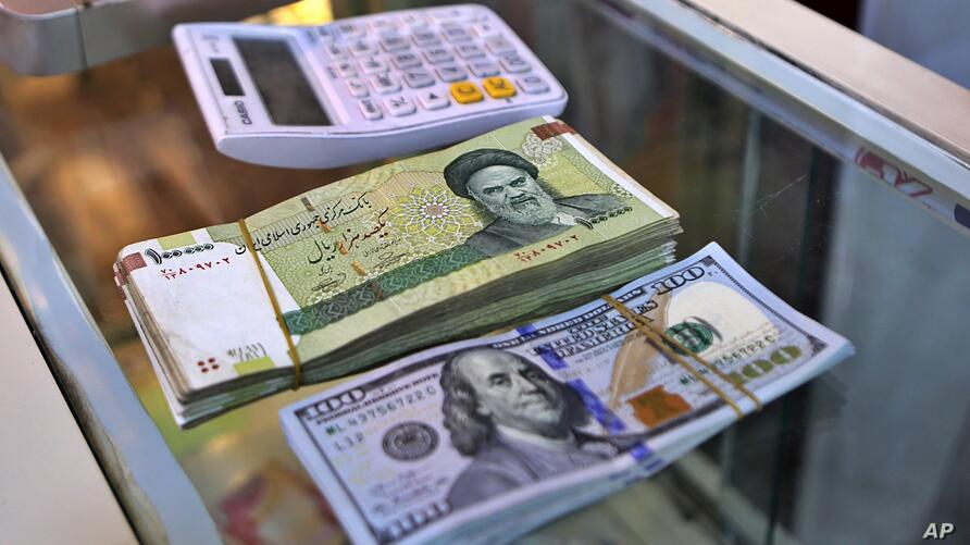 In this Wednesday, May ۲۱, ۲۰۱۹, photo, U.S. and Iranian currency are readied by a money exchanger outside the golden-domed…