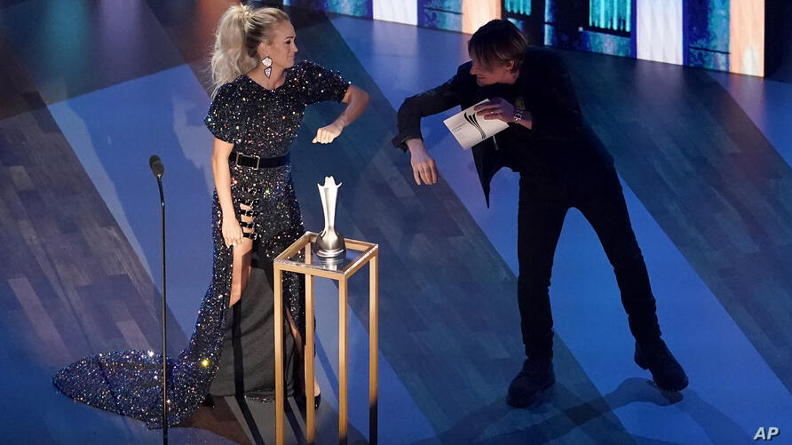 Carrie Underwood, left, winner of the entertainer of the year award, elbow bumps host Keith Urban on stage during the 55th…