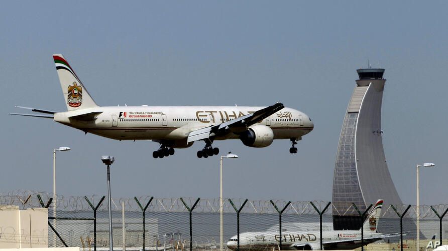 FILE - In this May 4, 2014 file photo, an Etihad Airways plane prepares to land at the Abu Dhabi airport in the United Arab…