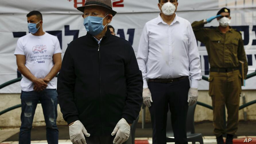 Holocaust survivor Shalom Stamberg, second left, wears a mask and keeps a safe distance from others during a two-minute-long…