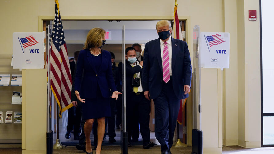 President Donald Trump walks with Wendy Sartory Link, Supervisor of Elections Palm Beach County, after casting his ballot for…
