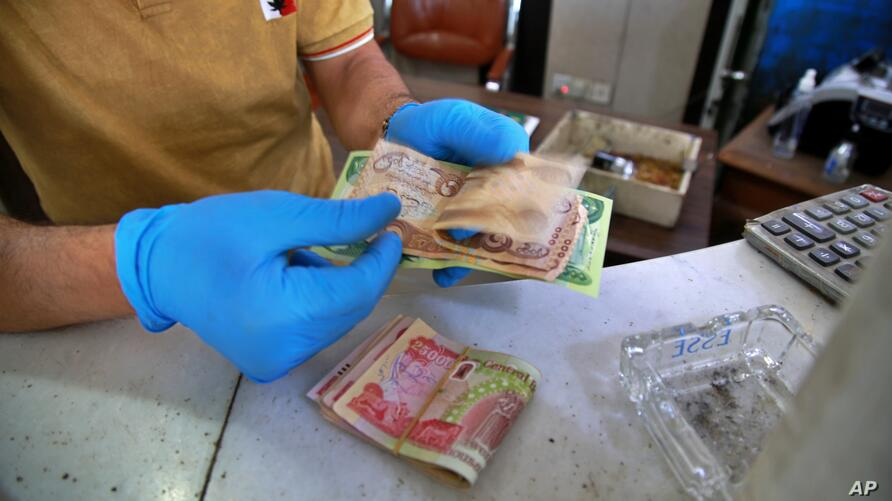 In this Sunday, May, 3, 2020, an Iraqi money changer counts banknotes in Baghdad, Iraq. The pandemic has also reawakened debate…