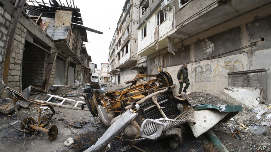 A man walks in the yard of an apartment building damaged by shelling by Azerbaijan's artillery during a military conflict in…