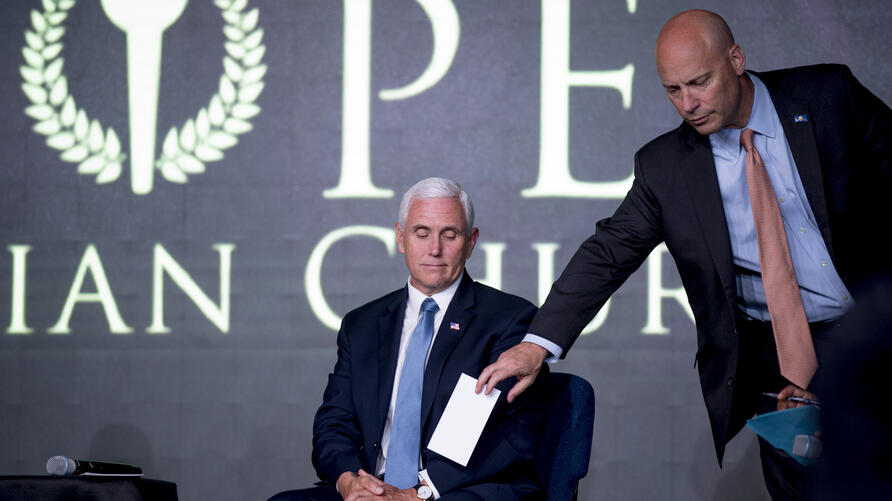 Vice President Mike Pence's Chief of Staff Marc Short, right, hands a note to Vice President Mike Pence, left, as he meets with…