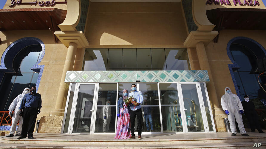 Jordanian newly-weds pose with flowers at the entrance of a Dead Sea resort where they have been quarantined for 14 days,…