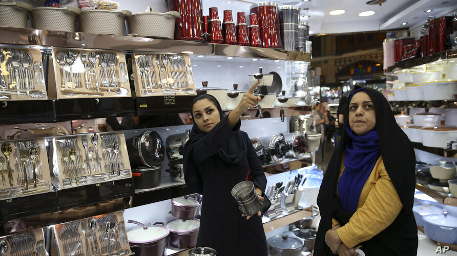 In this Thursday, Sept. ۶, ۲۰۱۸, photo, Kiana Ismaili, ۲۶, left, shops with her mother at a kitchenware shop ahead of her…