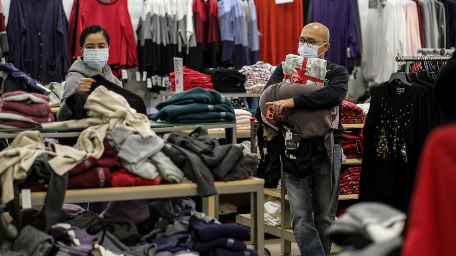 Black Friday shopper Alex Gamboa, right, 58, of Los Angeles, holds merchandises as his wife, who did not give her name, checks…
