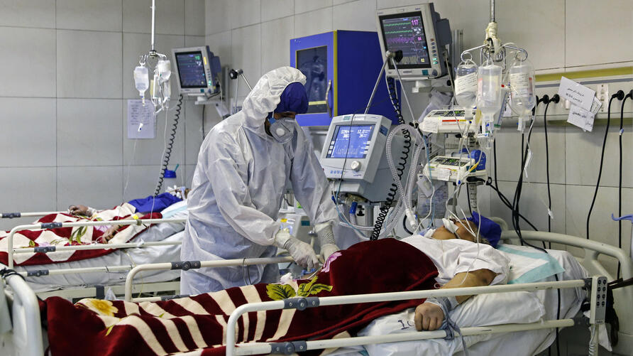 FILE - In this March 1, 2020 file photo, a medic treats a patient infected with coronavirus, at a hospital in Tehran, Iran…