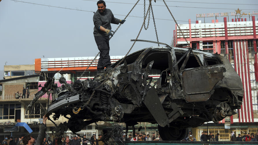 Afghan security personnel oversee the removal of damaged vehicles after a bombing attack in Kabul, Afghanistan, Sunday, Dec. 20…