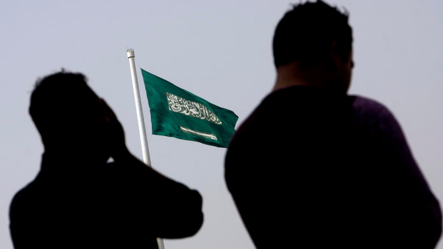 People pray at an open air makeshift mosque in front of a giant Saudi Flag in Jiddah, Saudi Arabia, Wednesday, June 21, 2017…