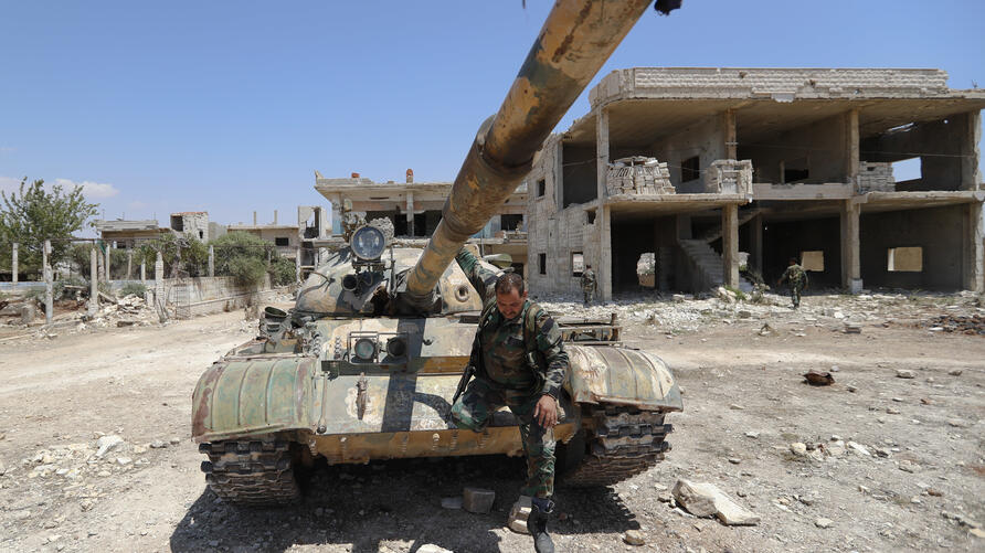 A Syrian soldier jumps from a tank at his military post overlooking the Damascus-Aleppo highway in the central Syrian town of…