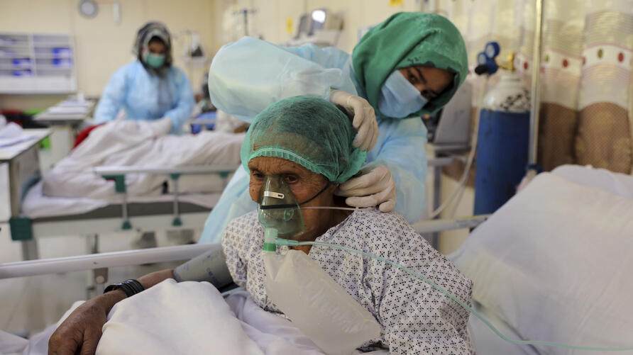 An Afghan doctor checks a COVID-19 patient at the Afghan-Japan Communicable Disease Hospital in Kabul, Afghanistan, Thursday,…