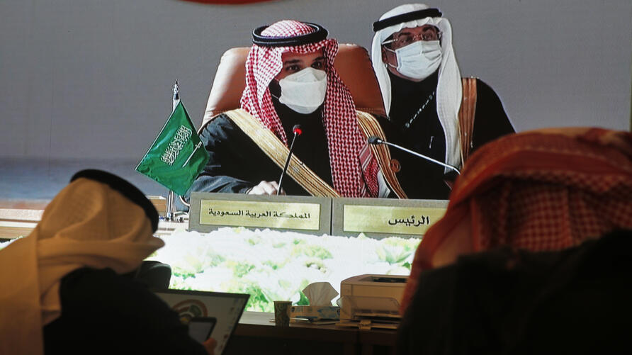 Journalists watch a large display screen in a press center, as Saudi Crown Prince Mohammed bin Salman, center left, chairs the…