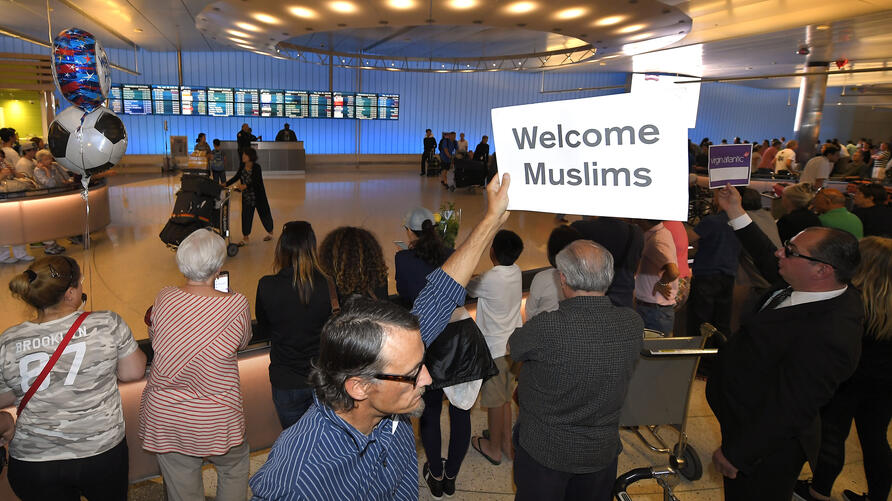 John Wider holds up a sign welcoming Muslims in the Tom Bradley International Terminal at Los Angeles International Airport,…