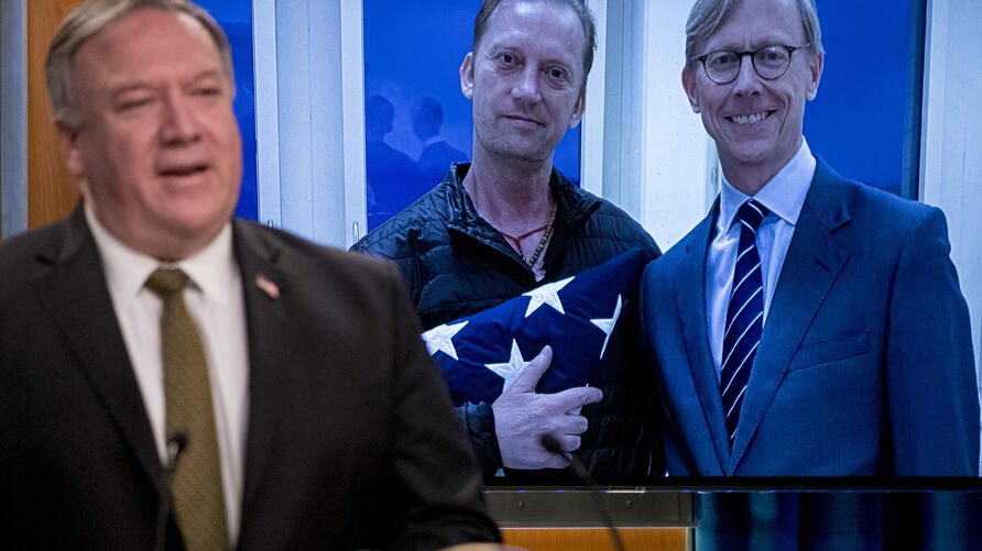 An image of Michael White, center, posing with U.S. special envoy for Iran Brian Hook, released after being detained for two…