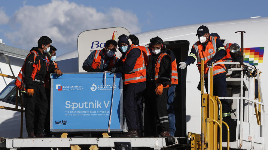 Airport employees unload the first shipment of Russia's Sputnik V COVID-19 vaccine after it arrived at the international…