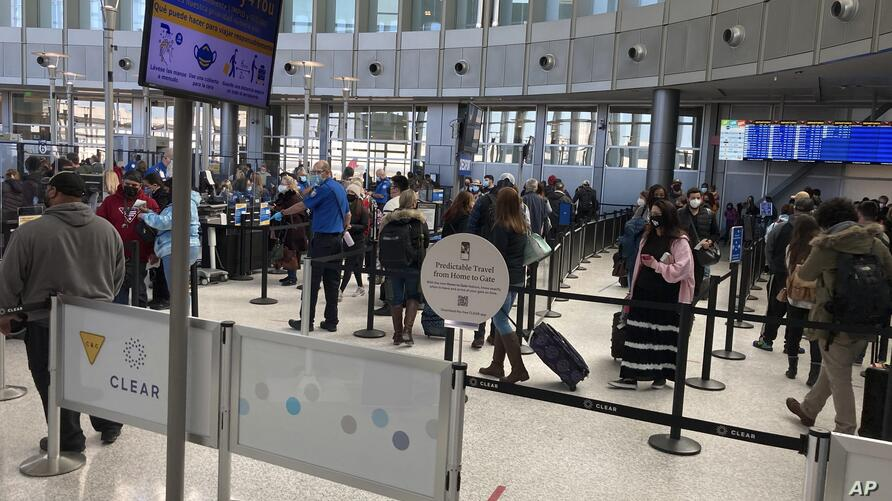 Travelers stand in line at a TSA security checkpoint at Austin-Bergstrom International Airport Friday, Feb. 19, 2021, in Austin…
