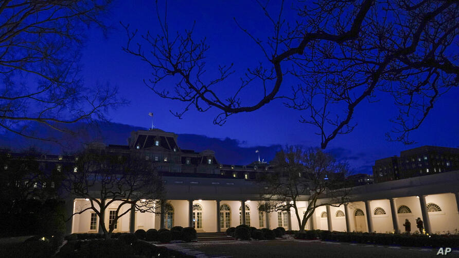 Lights shine on the West Wing Colonnade of the White House at dusk, Saturday, Feb. 20, 2021, in Washington. (AP Photo/Patrick…