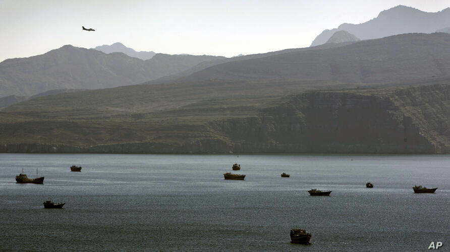 FILE - In this Jan. 19, 2012 file photo, a plane flies over the mountains in south of the Strait of Hormuz as the trading dhows…