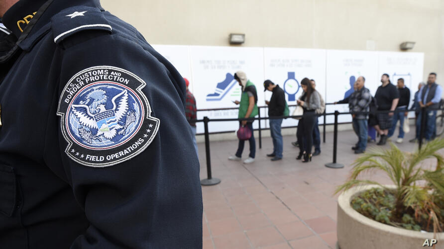 FILE - In this Dec. 10, 2015, file photo, pedestrians crossing from Mexico into the United States at the Otay Mesa Port of…