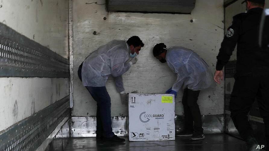 Medics check a shipment of the Russian Sputnik V vaccine inside a truck at the Kerem Shalom border crossing, in Rafah, Gaza…
