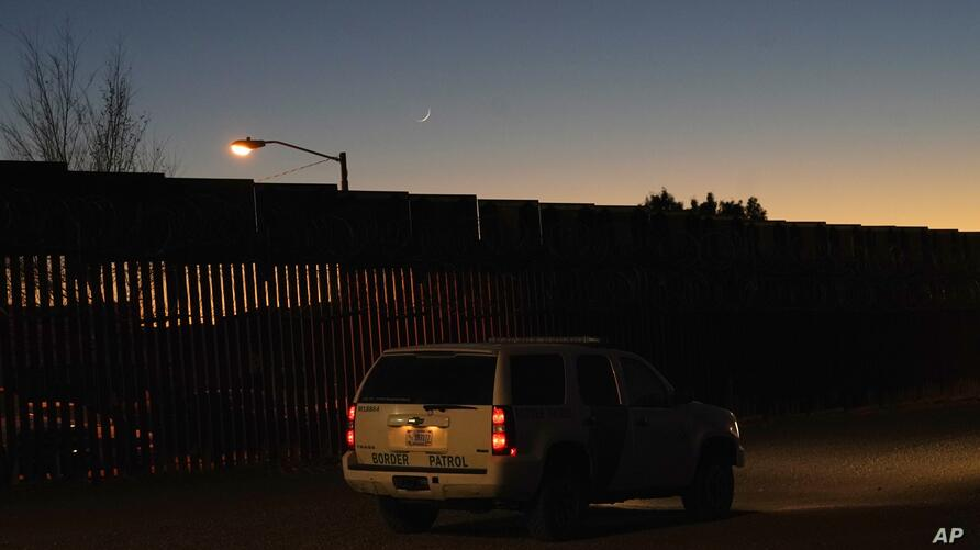 A U.S. Border Patrol vehicle sits parked near where a Las Posadas event at the U.S.-Mexico border wall took place, as several…